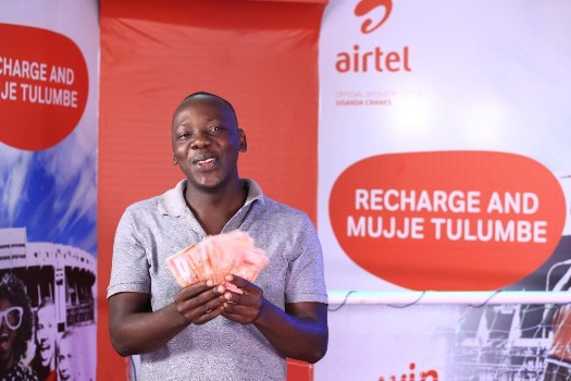 Sembatya Vincent, Fruit Vendor from Wakiso pose for a photo with his UGX 1,000,000 he won in the Recharge Promotion