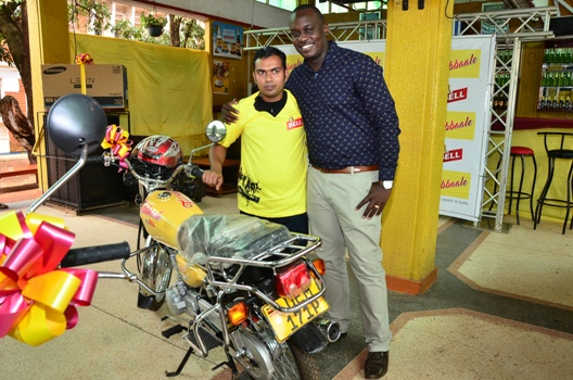 Brian Seruyiggo (R), Customer Marketing Manager-Bell Lager congratulates Ali Asjan (L), a motorcycle winner in the UBL Tubbaale promotion at UMA Show grounds