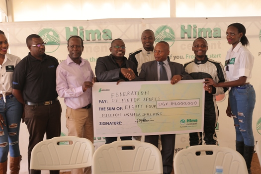 Allan Ssemakula (C), the Hima Cement Marketing Director hands over a dummy cheque to Dusman Okee, the FMU President during the Pearl of Africa Rally Press Briefing