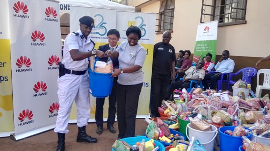 Ms Doris Akol, the Commissioner general of URA hands over food to Kampala Metropolitan Traffic Commander, Mr. Norman Musinga as Chen Jing, Huawei Chief Financial Officer witnesses
