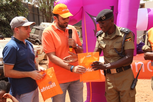 Africell Marketing Executive- Marc Aad together with Commercial Director Milad Khairallah hand over phones to SP Philbert Waibi the Kira Road Police Commander